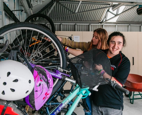 Two young people grabbing some bicycles from a rack in a garage